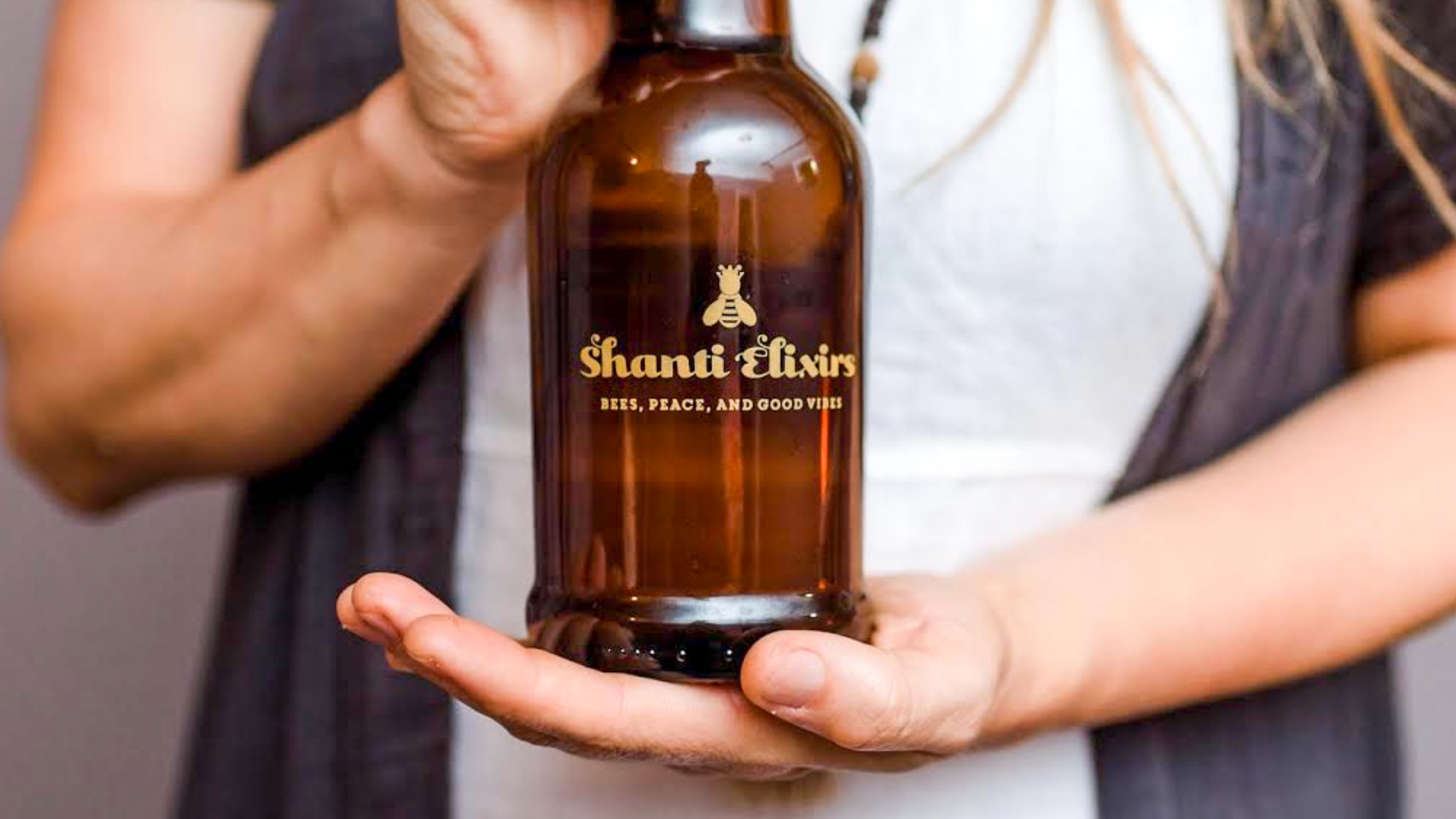person holding a mini growler of Shanti Jun